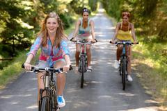 Three female friends riding bikes in park - stock photo