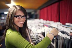 attractive young woman smiling while looking at records in a music store - stock photo