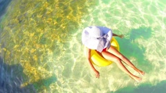 summer concept, female enjoy relaxing on inflamable rubber ring, aerial hd - stock footage