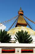 stupa with buddha eyes and prayer flags on clear blue sky backgr - stock photo