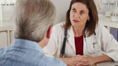 Senior doctor advising elderly patient Stock Footage