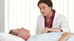Senior doctor listening to mature patient's heart - stock footage