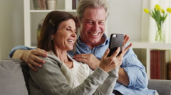 Sweet senior couple using smartphone on couch Stock Footage