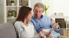 Senior couple using tablet to make a purchase Stock Footage