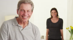 Happy Elderly couple standing in living room looking at camera Stock Footage