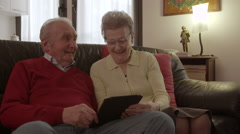 Elder senior couple browsing and watching videos on a tablet Stock Footage