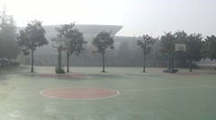 Empty basketball playground on a foggy day in a high school Stock Footage