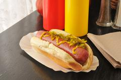Hot dog with mustard and relish - stock photo