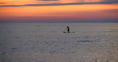Paddle board standing paddling paddleboard boarding surfboard stand up sunset Stock Footage