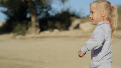 Little blond girl throwing stones into the water Stock Footage