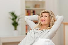 Woman relaxing at home with a contented smile Stock Photos