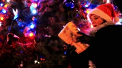 Beautiful woman in a fur coat and santa hat near christmas tree receives gift. Stock Footage