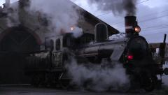 Preserved steam locomotive leaves the engine-shed one early December morning Stock Footage
