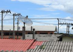 Satellite dish and tv antennas on the house roof with electricity post Stock Photos