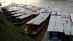 Parking a long-tail boat in-between other long-tail boats at the Mekong River Stock Footage