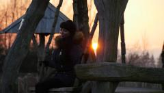 Tired but happy woman on swing at evening winter sunset Stock Footage