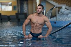 young looking macho man at hotel indoor pool - stock photo