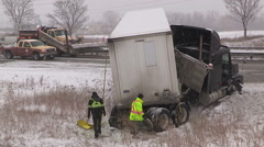 Tractor trailer crash on icy snow covered highway in winter storm - stock footage