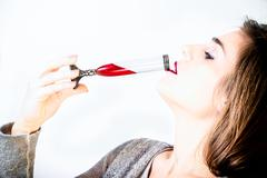 Woman drinks red poison Stock Photos