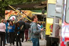 people wait in line to buy meals from food trucks - stock photo