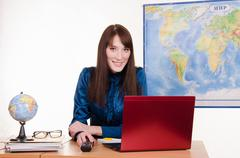 girl behind the desk in office of travel agency - stock photo