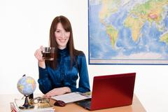manager a travel agency with mug of tea in hand - stock photo
