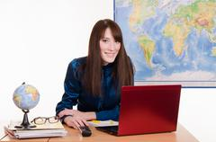 Stock Photo of young girl working on a laptop in the office of travel agency
