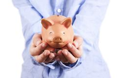 hands holding pink pig piggy bank, economics and finance - stock photo