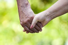 Clasped hands of older people with natural background Stock Photos