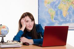 Young teacher of geography has earned for laptop Stock Photos
