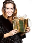 Exclusive lady in a fur coat holding a gold gift Stock Photos