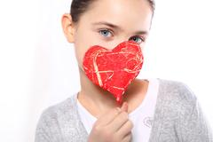 Caucasian girl with red Valentine heart  - stock photo