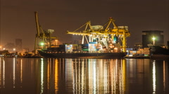 Night to day of  container cargo freight ship with working crane bridge in sh Stock Footage