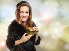 Exclusive lady in a fur coat holding a gold gift - stock photo