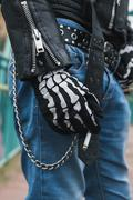 detail of a guy wearing skeleton gloves - stock photo