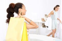 Women buy shoes at a shoe store, mulatto and Caucasian  Stock Photos