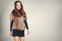 Pretty brunette in a vest with fur - stock photo