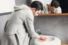 Young man washing his hands - stock photo