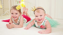 Two little cute sisters with crown on heads lying on the bed - stock footage