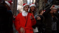 A young man and woman smoke cigarettes while dressed as Santa Claus Stock Footage