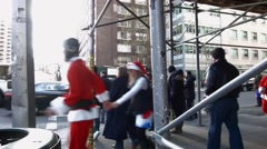 Many young men and women dressed as Santa Claus cross under scaffolding Stock Footage