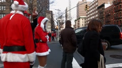 A few young men and women dressed as Santa Claus wait to cross traffic Stock Footage