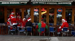 "Young men dressed as Santa Claus say ""happy SantaCon"" Stock Footage"