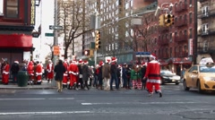 Many young men and women dressed as Santa Claus wait to cross a intersection Stock Footage