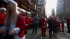 Hundreds of young men and women dressed as Santa Claus wait on a busy sidewalk Stock Footage