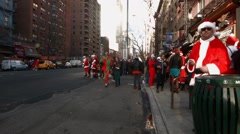 A wide shot of young men and women dressed as Santa Claus crossing a busy street Stock Footage