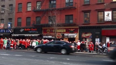 A wide shot of hundreds of young men and women dressed as Santa Claus Stock Footage