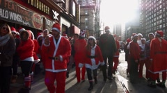 Many young men and women dressed as Santa Claus wait on the sidewalk Stock Footage