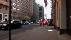 Several Young men and women dressed as Santa Claus walk along side traffic Stock Footage