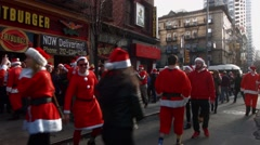 Hundreds of men and women dressed as Santa Claus wait on the sidewalk Stock Footage